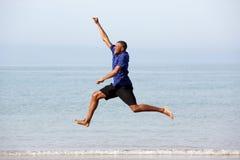 Portret z podnieceniem młody afrykański faceta doskakiwanie wzdłuż morza i bieg Zdjęcie Royalty Free