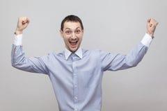 Portret z podnieceniem radosny przystojny szczecina biznesmen w klasycznej bławej koszulowej pozycji z nastroszonymi rękami i odś obraz stock