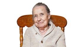 Portret z włosami starsza kobieta, babcia, siedzi na rocznika brązu krześle, odizolowywa białego tło Pojęcie opieka, obraz royalty free