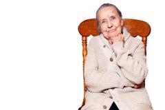Portret z włosami starsza kobieta, babcia, siedzi na rocznika brązu krześle, odizolowywa białego tło Pojęcie opieka, fotografia royalty free