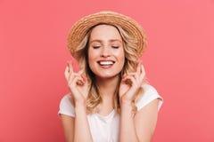 Portret zadowolona blond kobieta 20s jest ubranym s?omianego kapelusz utrzymuje palce krzy?uj?cy i ?yczy dla szcz??cia obraz royalty free
