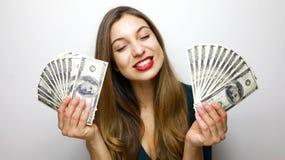 Portret zadowolona młoda kobieta trzyma wiązkę pieniędzy banknoty odizolowywający nad białym tłem fotografia stock