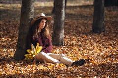 Portret zadumana brunetki dziewczyna w jesień spadku parku w kapeluszu, pulowerze i spodniach brown, kobiety obsiadanie na liścia zdjęcie stock