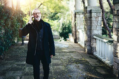 Portret zadumany wieka średniego biznesmen opowiada na jego smartphone podczas gdy chodzący w miasto parku Horyzontalny, zamazany Fotografia Stock
