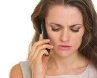 Portret zaniepokojonej kobiety opowiada telefon komórkowy Zdjęcie Stock