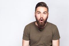 Portret zdziwiony brodaty mężczyzna z ciemnozieloną t koszula przeciw światłu - szary tło fotografia royalty free