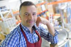 Portret zekere fabrikant die zich door opslagtank bevinden in brouwerij Royalty-vrije Stock Foto's