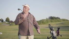 Portret zekere succesvolle rijpe mens die zich met een golf clubon een golfcursus in goed zonnig weer bevinden Sport en stock footage