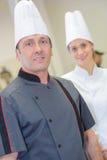 Portret zekere vrouwelijke en mannelijke chef-kok in keuken Royalty-vrije Stock Afbeeldingen