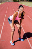 Portret zmęczona żeńskiej atlety pozycja na bieg śladzie Zdjęcie Royalty Free
