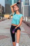 Portret zmęczona młoda sprawności fizycznej kobieta bierze przerwę od działania, obcieranie pot od jej czoła, słucha zdjęcie stock