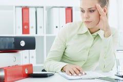 Portret zmęczony bizneswoman patrzeje stertę falcówki na biurku Zdjęcia Royalty Free