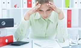 Portret zmęczony bizneswoman patrzeje dokumenty na biurku Zdjęcia Stock