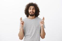 Portret zmartwiony przystojny latynoski facet z afro fryzurą w pasiastej koszulce, zjadliwej wardze i skrzyżowaniu, z niepokojem Zdjęcie Stock