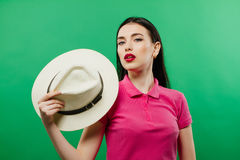 Portret Zmysłowa Ciemnowłosa dziewczyna z kowbojskim kapeluszem w ręce Pozuje w studiu na Zielonym tle Fotografia Royalty Free