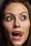 Portret zmysłowa piękna młoda kobieta pokazuje długiego jęzor Zdjęcia Stock
