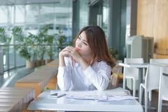 Portret zrelaksowany młody Azjatycki pracownik patrzeje daleki w biurze obrazy royalty free