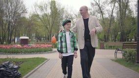 Portreta ?liczny dziad i uroczy wnuk chodzi kamera w parku Pokolenia poj?cie c?rki ekspresyjnego rodzinnego ojca ?yczliwi mum far zdjęcie wideo