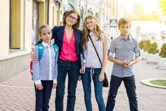 Portreta żeński nauczyciel z dziećmi stoi outside szkoły fotografia stock