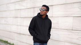 Portreta afrykański mężczyzna w czarnym hoodie, okulary przeciwsłoneczni chodzi na miasta uliczny patrzeć daleko od zdjęcia royalty free