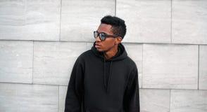 Portreta afrykański mężczyzna w czarnym hoodie, okulary przeciwsłoneczni patrzeje daleko od na miasto ulicie nad szarą ścianą z c obrazy royalty free