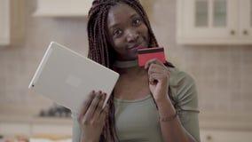 Portreta amerykanin afrykańskiego pochodzenia śliczna uśmiechnięta kobieta stoi w kuchni z pastylką w rękach z dreadlocks Dama zdjęcie wideo
