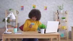 Portreta amerykanin afrykańskiego pochodzenia kobieta z kartą kredytową w jego rękach szuka internet na komputerze zbiory