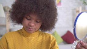 Portreta amerykanin afryka?skiego pochodzenia kobiety pozytywny makija? patrzeje w lustrze w nowo?ytnym mieszkaniu zbiory wideo