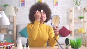 Portreta amerykanin afrykańskiego pochodzenia kobiety pozytywny makijaż patrzeje w lustrze w nowożytnym mieszkaniu zamkniętym w g zbiory