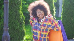 Portreta amerykanin afrykańskiego pochodzenia rozochocona kobieta z afro fryzurą z pakunkami po robić zakupy wolnego mo zbiory