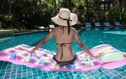 Portreta beautifu kobieta relaksuje w dużego kapeluszu i bikini Siedzącym b Fotografia Stock