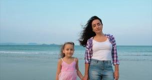 Portreta clouse w górę matki i córka chodzimy wzdłuż wybrzeża Szczęśliwy rodzinny odprowadzenie na dennym wybrzeżu zdjęcie wideo