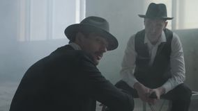 Portreta dwa eleganccy m??czy?ni siedzi w zaniechanym budynku dyskutuje biznes w kapeluszach Mafijni faceci spotkania w zdjęcie wideo