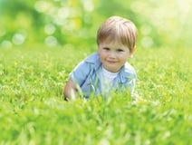 Portreta dziecka śliczny uśmiechnięty lying on the beach na trawie w pogodnym letnim dniu zdjęcia royalty free
