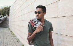 Portreta elegancki afrykański mężczyzna patrzeje daleko od w czarnych okularach przeciwsłonecznych, chodzący na miasto ulicie obrazy stock
