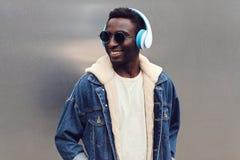 Portreta elegancki miastowy uśmiechnięty afrykański mężczyzna w hełmofonach cieszy się słuchać muzyka na szarym metal ściany tle zdjęcie stock