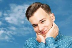 Portreta faceta Biali śliczni młodzi uśmiechy Mężczyzna ubierał w błękitnej koszula, ściska jego twarz z jego rękami Mężczyzna na obrazy stock