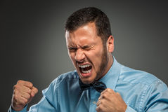 Portreta gniewny wzburzony młody człowiek w błękitnej koszula, motyli krawat Zdjęcie Stock