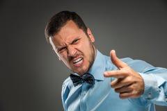 Portreta gniewny wzburzony młody człowiek w błękitnej koszula, motyli krawat Zdjęcia Royalty Free