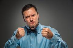 Portreta gniewny wzburzony młody człowiek w błękitnej koszula, motyli krawat Zdjęcie Royalty Free