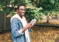 Portreta kreatywnie uśmiechniętego afrykańskiego mężczyzna czytelnicza książka w jesieni obraz royalty free