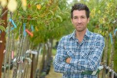 Portreta mężczyzna między owocowymi drzewami Fotografia Stock