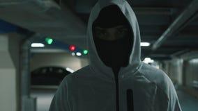 Portreta mężczyzna w czarnym balaclava chodzi menacingly i patrzeje przy kamerą zdjęcie wideo