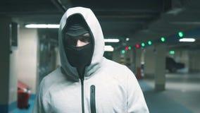 Portreta mężczyzna w czarnym balaclava chodzi menacingly i patrzeje przy kamerą Wolny mo zbiory