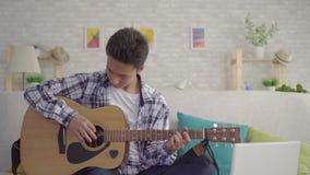 Portreta mężczyzny młody azjatykci muzyk bawić się gitarę zbiory wideo