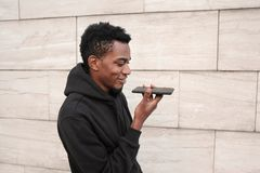 Portreta mężczyzny uśmiechnięty afrykański mienie w ręki smartphone używać głosu nakazowego pisaka, asystenta lub dzwonić, obrazy stock