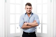 Portreta młodego człowieka przypadkowa pozycja w drzwi domu wnętrzu na lekkim tle uśmiechniętym i patrzeje kamera z Fotografia Stock