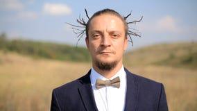 Portreta młody człowiek w ekstrawaganckim wizerunku w tle łąka zbiory wideo