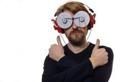 Portreta młody człowiek z szkłami słucha muzyczne aprobaty Obrazy Stock