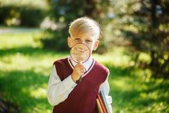Portreta mały uczeń na natury tle Dziecko z książkami i loupe Edukacja dla dzieciaków tylna koncepcji do szkoły Zdjęcia Stock